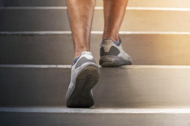 Pés de corredor correndo nas escadas close-up no sapato