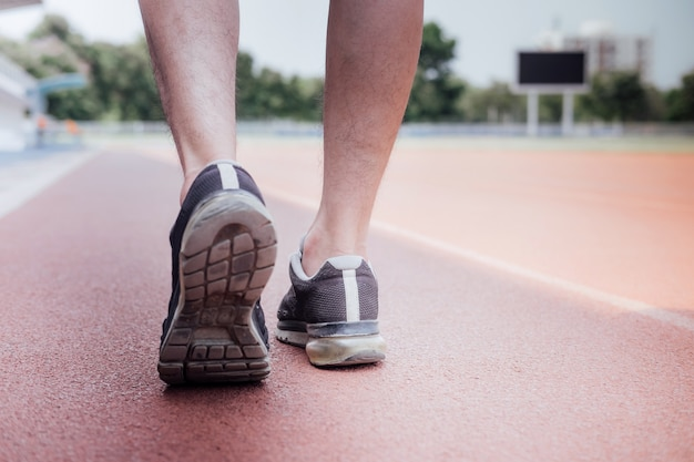 Pés de corredor de atleta correndo na pista de estrada