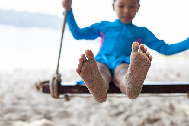 Pés de criança com areia enquanto ela jogando em um balanço na praia perto do mar em férias de verão