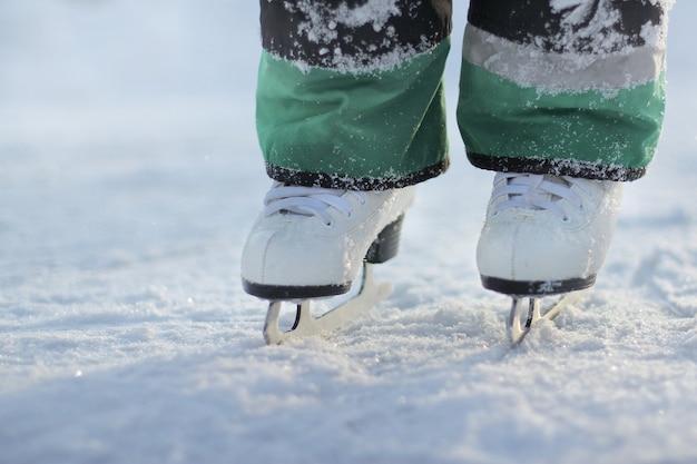 Pés de criança em patins brancos ficam no gelo. patinação no gelo em um dia gelado de inverno.