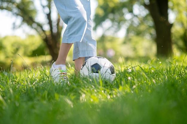 Pés de criança júnior com bola de futebol na grama