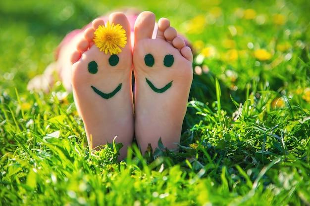 Pés de criança na grama desenhando um sorriso