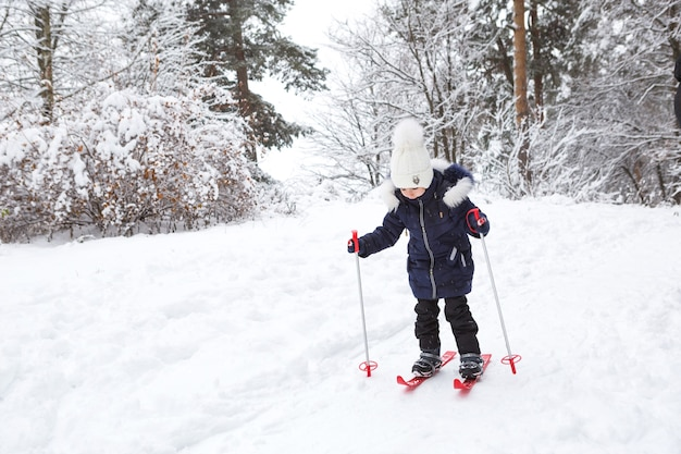 Pés de crianças em esquis de plástico vermelho com varas atravessam a neve de um escorregador - um esporte de inverno