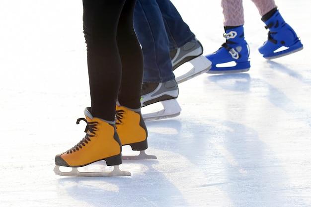 Pés de diferentes pessoas patinando na pista de gelo. esporte e entretenimento. descanso e férias de inverno.