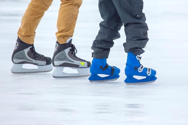 Pés de diferentes pessoas patinando na pista de gelo. hobbies e esportes