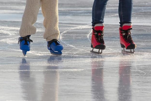 Pés de diferentes pessoas patinando na pista de gelo