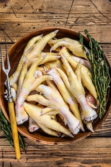 Pés de frango fresco cru em prato de madeira