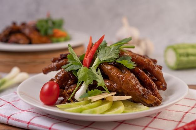 Pés de frango frito doce em um prato branco com coentro, pimenta, pepino e tomate.