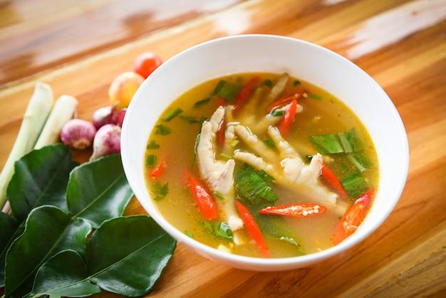 Pés de frango sopa picante pé de frango com uma tigela de sopa quente e azeda com legumes frescos