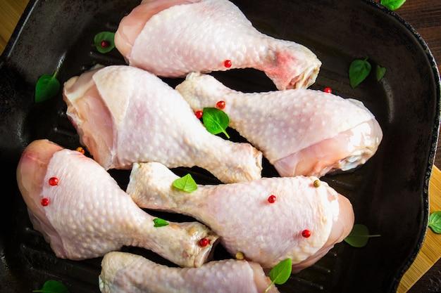 Pés de galinha crus em uma frigideira em uma tabela de madeira. ingredientes da carne para cozinhar. vista do topo.