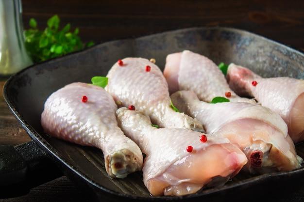 Pés de galinha crus em uma frigideira em uma tabela de madeira. ingredientes da carne para cozinhar.