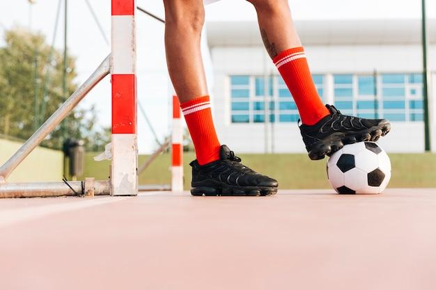 Pés de homem chutando futebol no estádio