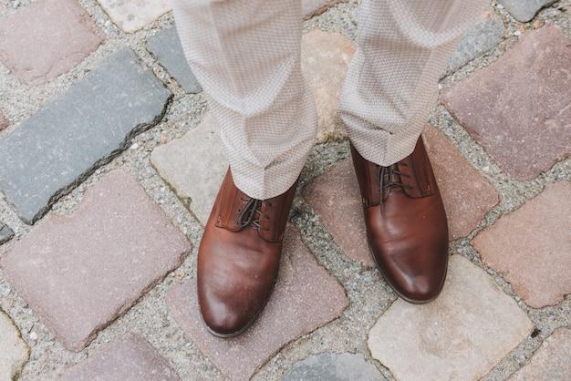 Pés de homem em lindos sapatos marrons polidos de oxford