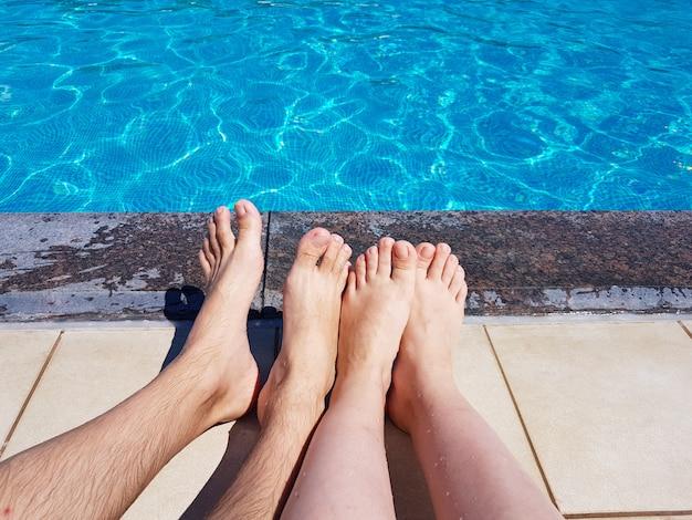 Pés de homens e mulheres à beira da piscina em um fundo de água azul em um dia de verão. descanse, viaje