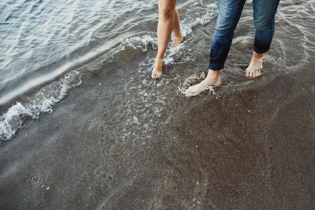 Pés de homens e mulheres vão na praia perto do mar