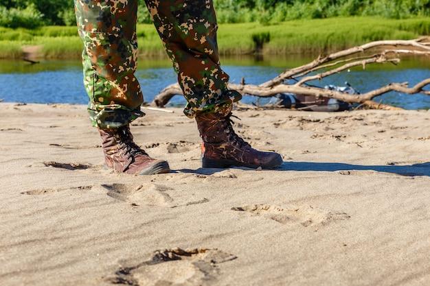 Pés de homens em botas à beira do rio
