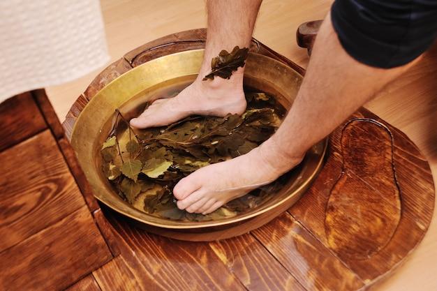 Pés de homens em um banho de pedicure com folhas de carvalho. cuidados com os pés e unhas