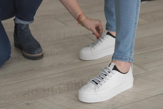 Pés de jeans e tênis branco