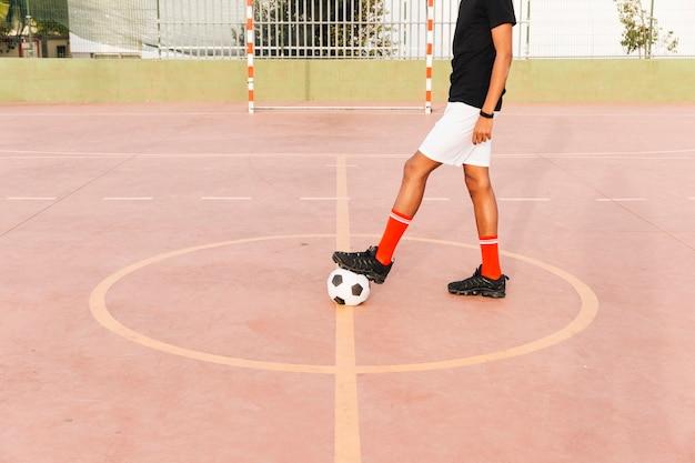 Pés de jogador de futebol na bola de futebol no estádio