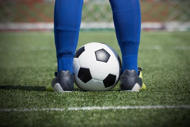Pés de jogador de futebol na bola