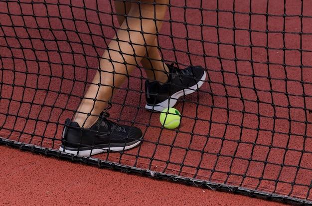Pés de jogador de tênis ao lado da rede