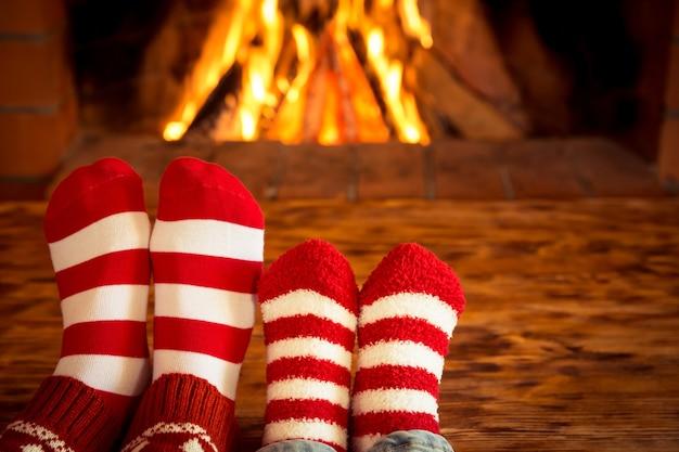 Pés de mãe e filho em meias de natal perto da lareira pessoas relaxando em casa férias de inverno