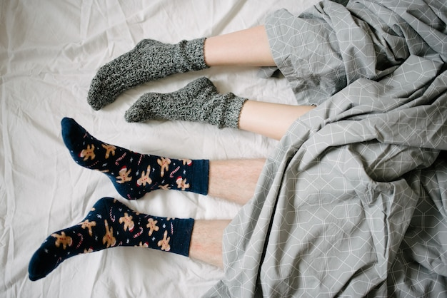 Pés de meias debaixo de um cobertor na cama