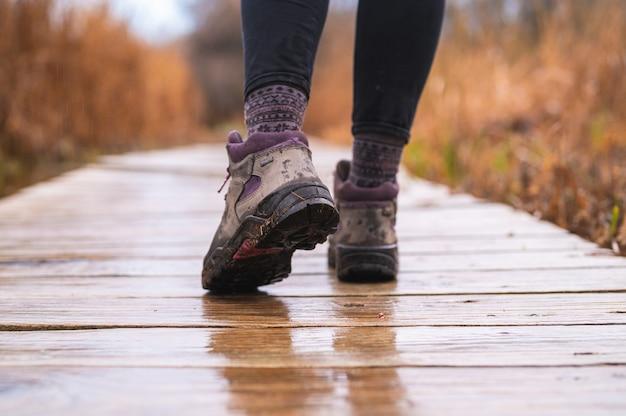 Pés de menina andando no calçadão de madeira com botas de caminhada em dia chuvoso