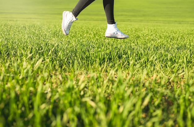 Pés de menina de tênis branco pulando em um prado verde na primavera