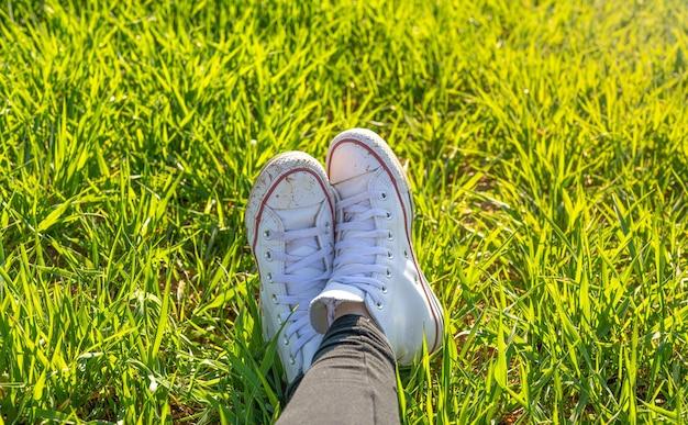 Pés de menina de tênis branco sentada em um prado verde na primavera em um dia muito ensolarado