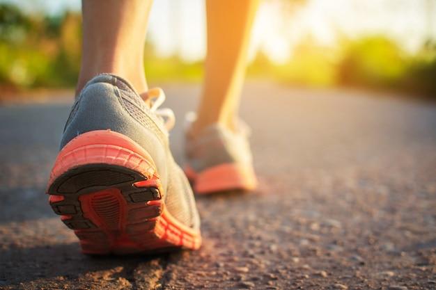Pés de mulher andando e exercício na estrada durante o pôr do sol.