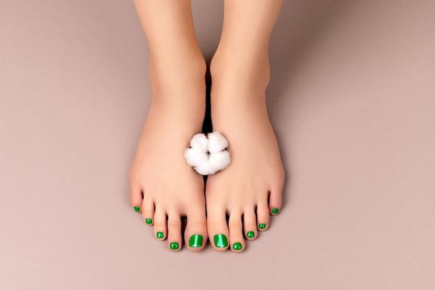 Pés de mulher bonita com unhas verdes segurando uma flor branca
