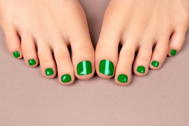 Pés de mulher bonita com unhas verdes