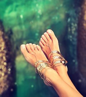 Pés de mulher bronzeados e bem tratados usando pulseiras no estilo boho acima da água do mar tropical