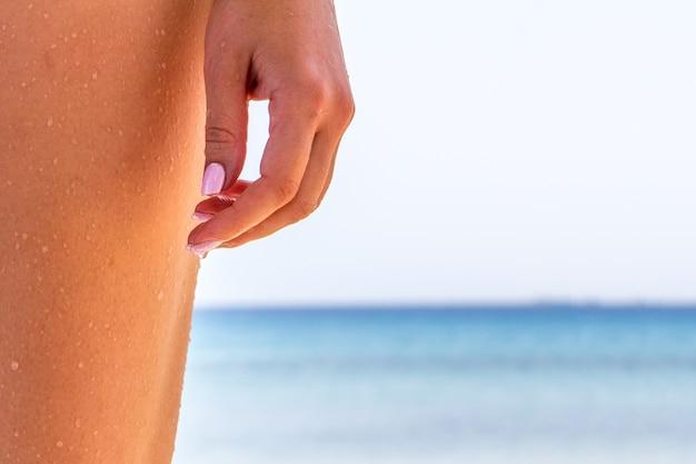 Pés de mulher closeup de garota relaxante na praia, aproveitando o sol no verão ensolarado