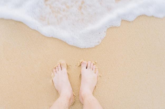 Pés de mulher com ondas correndo para a praia