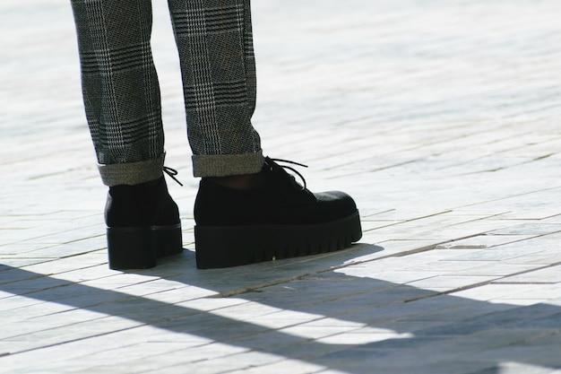 Pés de mulher com sapatos pretos de plataforma alta e calça cinza na rua