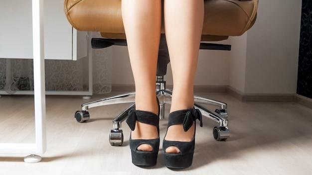 Pés de mulher de negócios sexy em meias e sapatos de salto alto atrás da mesa de escritório.