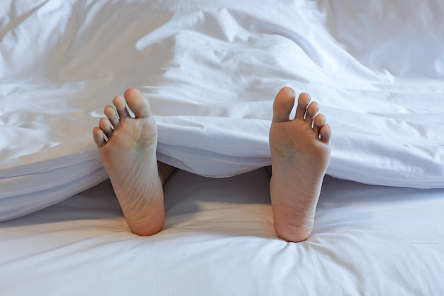 Pés de mulher dormindo no quarto da cama branca