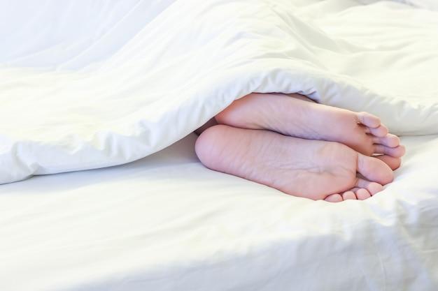Pés de mulher dormindo no quarto de cama branca