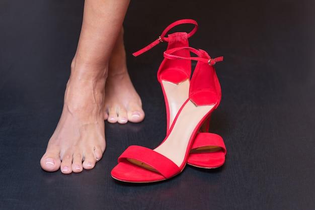 Pés de mulher e sandálias vermelhas