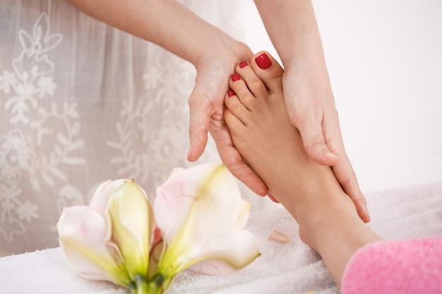 Pés de mulher em decorações de salão de beleza, recebendo massagem relaxante agradável