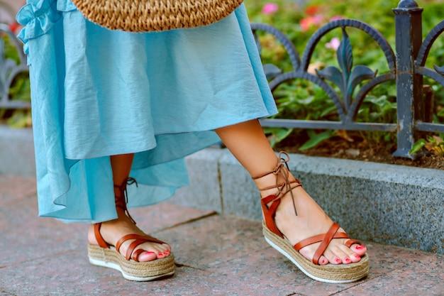 Pés de mulher em elegantes sandálias de gladiador