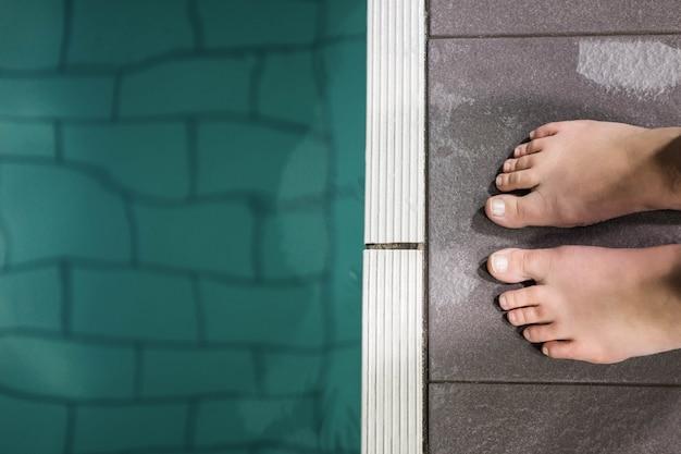 Pés de mulher em pé na beira da piscina no centro de lazer