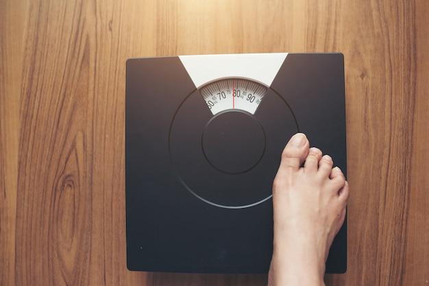 Pés de mulher em pé na escala de peso em fundo de madeira