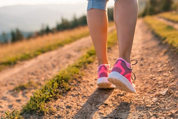Pés de mulher feminina corredor atleta correndo na estrada da montanha sob a luz solar.