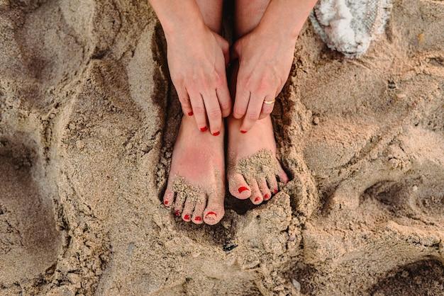 Pés de mulher na areia de uma praia