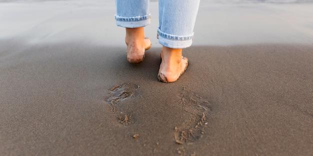 Pés de mulher na areia na praia