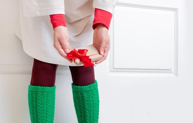 Pés de mulheres com meias verdes ficam perto da porta branca com presentes