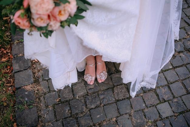 Pés de noiva sapatos buquê pedra estrada fora